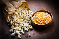 bowl of popcorn and kernelson a wooden table Royalty Free Stock Photos