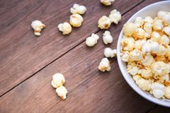 A bowl of popcorn on a wooden table. stock image