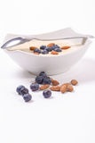 Bowl of porridge with berries. Bowl of oatmeal porridge with walnuts  and blueberry on the withe background Stock Images