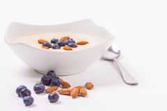 Bowl of porridge with berries. Bowl of oatmeal porridge with walnuts  and blueberry on the withe background Royalty Free Stock Photo