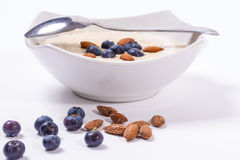 Bowl of porridge with berries. Bowl of oatmeal porridge with walnuts  and blueberry on the withe background Royalty Free Stock Photos