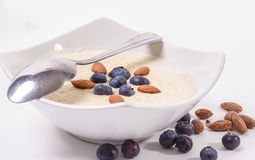 Bowl of porridge with berries. Bowl of oatmeal porridge with walnuts  and blueberry on the withe background Stock Photography