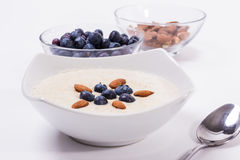 Bowl of porridge with berries. Bowl of oatmeal porridge with walnuts  and blueberry on the withe background Royalty Free Stock Images