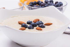 Bowl of porridge with berries. Bowl of oatmeal porridge with walnuts  and blueberry on the withe background Stock Photo