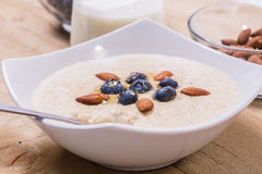 Bowl of porridge with berries. Bowl of oatmeal porridge with walnuts  and blueberry on the withe background Stock Photos