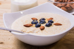 Bowl of porridge with berries. Bowl of oatmeal porridge with walnuts  and blueberry on the withe background Royalty Free Stock Image