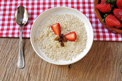 Bowl with porridge on a set table for breakfast Royalty Free Stock Image