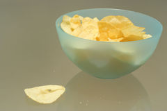 Bowl of Potato Chips. A bowl of potato chips ontop of a glass table with a bit of spill royalty free stock images