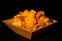 Bowl of potato chips. Close up shot of an unhealthily large wooden bowl of spicy potato chips or crisps on black background Stock Photo