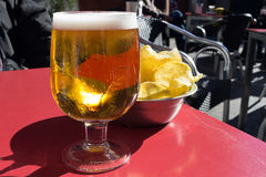 Bowl of potato chips and glass of light beer. Tapas and cerveza at outdoors cafe - Taken in Madrid royalty free stock photography