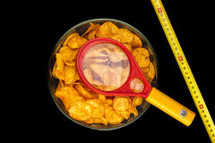 A bowl of potato chips with loupe and metering rule, isolated on Royalty Free Stock Photography