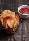 Bowl with potato crisps chips and ketchup on wooden board Royalty Free Stock Photos