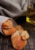 Bowl with potato crisps chips and olive oil on wooden board Royalty Free Stock Image
