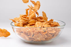 Bowl with pouring brown cereal flakes Royalty Free Stock Image