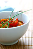 A bowl of prawn masala curry. Serve in white bowl garnish with springs of chives Royalty Free Stock Images