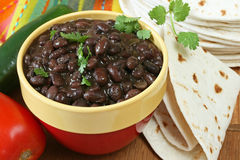 Bowl of prepared black beans with tortillas. Bowl of prepared black beans with flour tortillas and cilantro; tomato and jalapeno on side Stock Photo