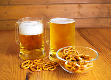 Bowl of pretzels and  two mugs of beer Royalty Free Stock Images
