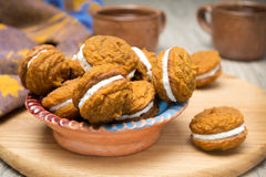 Bowl of pumpkin cookies with cream filling on a wooden board Stock Images