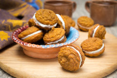 Bowl of pumpkin cookies with cream filling on a wooden board Royalty Free Stock Photography