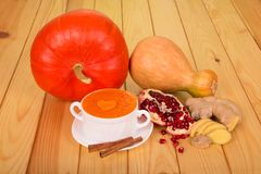 A bowl of pumpkin puree, two whole pumpkins, cinnamon sticks, po. Megranate seeds and ginger root against a light wood background Stock Photo