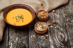 Bowl of pumpkin soup with bread crouton on dark wooden table. Bowl of pumpkin soup with bread crouton on the dark wooden table Stock Image