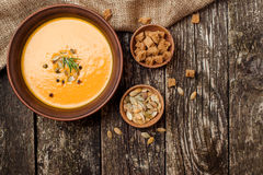Bowl of pumpkin soup with bread crouton on dark wooden table. Bowl of pumpkin soup with bread crouton on the dark wooden table Royalty Free Stock Photos