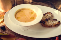 Bowl of pumpkin soup with bread crouton on wood Royalty Free Stock Images