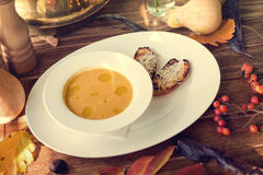 Bowl of pumpkin soup with bread crouton on wood Stock Photography