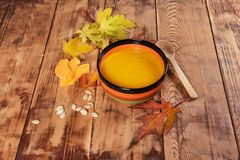 Pumpkin soup bowl on rustic wooden background Royalty Free Stock Photography