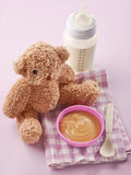 Bowl of pureed apple and baby milk bottle Royalty Free Stock Photos
