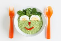 Green vegetables puree with boiled egg, food for kids. Bowl of pureed green vegetables for baby with happy face made by egg and vegetables Royalty Free Stock Photos