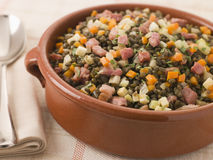 Bowl of Puy Lentils with Lardons. With a spoon on a table Stock Photography