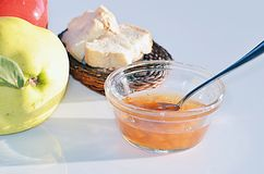 A bowl of jam, bread slices and  a quince. A bowl of quince jam with a spoon in it, slices of bread and a fresh quince Stock Images