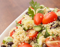 Closeup of healthy quinoa salad with fresh vegetables. Bowl of quinoa salad made with fresh vegetables and cilantro Stock Photos