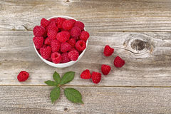 Bowl of Raspberries on aged wood. Top view image of fresh Raspberries in white bowl, some falling out, on rustic wood with leaf Stock Images