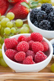 Bowl of raspberries, fresh berries and green grapes. On a wooden tray, close-up, vertical, top view Stock Images