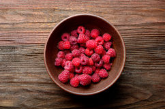 Bowl of raspberries. Overhead view of a bowl of raspberries on a grainy wooden table Royalty Free Stock Image