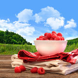 Bowl of raspberries on rustic table Stock Image