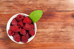 Bowl of raspberries on a table. Bowl of raspberries on an old wooden table stock images