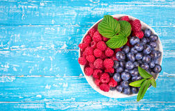 Bowl of raspberry and blueberry above Stock Images