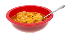 A bowl of ravioli with a spoon on a white background Royalty Free Stock Photo