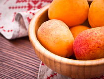 Bowl of raw apricots. Bowl of fresh raw apricots on a napkin with red pattern and on a wooden surface Stock Photo
