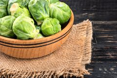 Brussels sprouts in bowl. Bowl with raw brussels sprouts on sackcloth and table closeup Royalty Free Stock Images