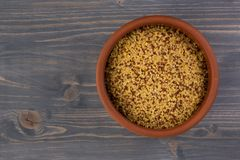 Bowl of raw bulgur and quinoa on wooden table stock images