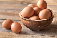 Bowl of raw chicken eggs. On the wooden background stock images