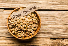 Bowl of raw coffee beans. Over an old wooden table Stock Photography