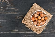 Hazelnuts in bowl. Bowl with raw hazelnuts in shell on sackcloth and table, top view Royalty Free Stock Image