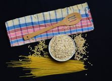 A bowl of raw oatmeal, cereals, pasta, wooden spoon and a towel on a black background. The cooking process. Preparation of morning breakfast Stock Image