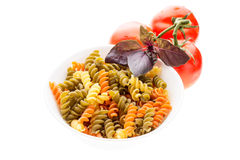 Bowl of raw pasta with basil and tomatoes Stock Photography