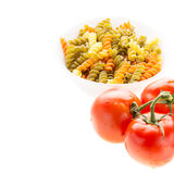 Bowl of raw pasta with basil and tomatoes Stock Photos